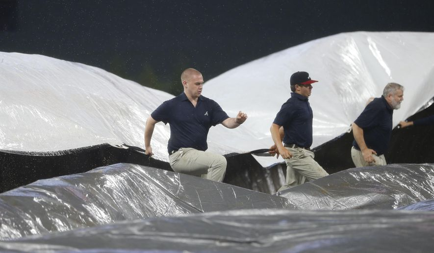 Members for the Atlanta Braves grounds crew work to cover the infield as rain begins to fall in the fourth inning of a baseball game against the New York Mets, Thursday, May 4, 2017, in Atlanta. (AP Photo/John Bazemore)
