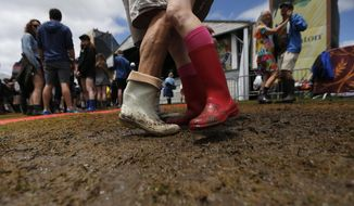 A couple dances in shrimp boots as Yvette Landry performs at the Fais Do-Do stage at the New Orleans Jazz and Heritage Festival in New Orleans, Thursday, May 4, 2017. (AP Photo/Gerald Herbert)