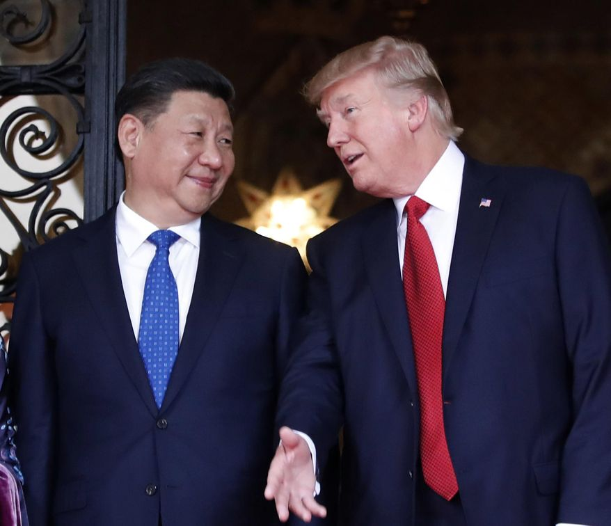 FILE - In this April 6, 2017 file photo, Chinese President Xi Jinping, left, smiles at U.S. President Donald Trump as they pose together with their wives for photographers before dinner at Mar-a-Lago in Palm Beach, Fla.  (AP Photo/Alex Brandon, File) **FILE**