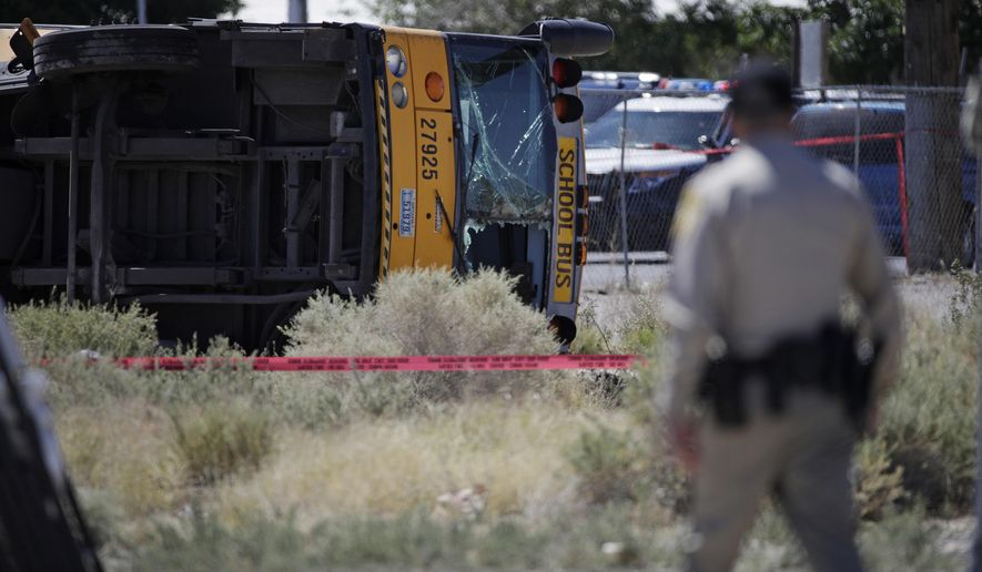 Authorities investigate a school bus crash Thursday, May 4, 2017, in Las Vegas. (AP Photo/John Locher)