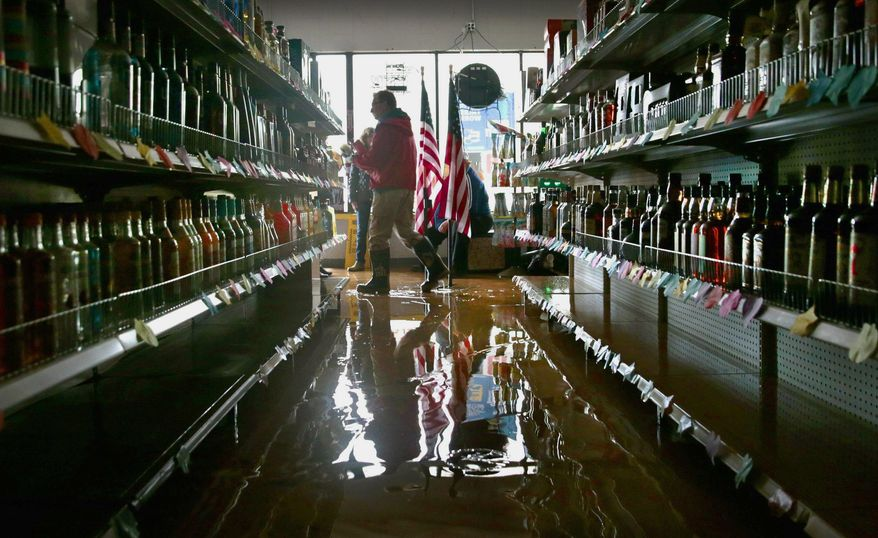Pacific building and fire inspectors look through Pacific Package Liquor to deem it safe for occupancy on E. Osage Street in Pacific, Mo., Wednesday, May 3, 2017. Heavy rains have swollen many rivers to record levels in parts of Missouri, Illinois, Oklahoma and Arkansas. Five deaths have been blamed on flooding in Missouri, while hundreds of people have been displaced and thousands more are potentially in harm's way. (Robert Cohen/St. Louis Post-Dispatch via AP)