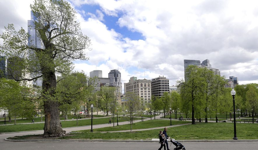 In this May 3, 2017 photo, a couple walks with a child in the Boston Common, a park surrounded by buildings in downtown Boston.  A city that has seen its share of strife, from the school desegregation to the gentrification of its working classed neighborhoods, now finds itself embroiled in a new battle over a skyscraper shadow and two cherished public parks, Boston Common and the neighboring Public Garden. At issue is whether developers of the proposed tower should be allowed to violate a state law banning buildings from casting shadows over historic parks. (AP Photo/Elise Amendola)