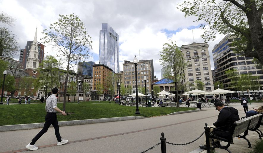 In this May 3, 2017 photo, people sit and walk in the Boston Common, a park surrounded by buildings in downtown Boston. A city that has seen its share of strife, from the school desegregation to the gentrification of its working classed neighborhoods, now finds itself embroiled in a new battle over a skyscraper shadow and two cherished public parks, Boston Common and the neighboring Public Garden. At issue is whether developers of the proposed tower should be allowed to violate a state law banning buildings from casting shadows over historic parks. (AP Photo/Elise Amendola)