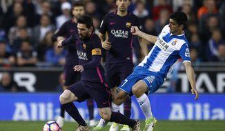 FC Barcelona's Lionel Messi, left, duels for the ball against Espanyol's Gerard Moreno during the Spanish La Liga soccer match between Espanyol and FC Barcelona at RCDE stadium in Cornella Llobregat, Spain, Saturday, April 29, 2017. (AP Photo/Manu Fernandez)