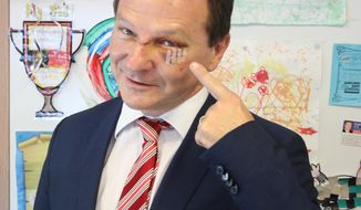 In this May 3, 2017, photo, Australian lawmaker Graham Perrett poses in his office in the city of Brisbane, Australia to show his injuries sustained three days earlier while watching the satirical U.S. TV series Veep at home. Perrett says he was stunned that he had grabbed the attention of Veep stars by simply laughing so hard at an episode of the political satire that he choked on his sushi and knocked himself unconscious on a kitchen bench. (AP Photo/Ben Driscoll)