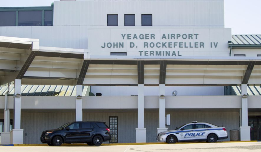 Police cruisers are parked outside the terminal at Yeager Airport in Charleston, W.Va after a fatal plane crash, Friday, May 5, 2017. A cargo plane contracted by UPS went off the runway and over a hillside at the West Virginia airport Friday morning, an airport official said.  (AP Photo/Ben Queen)