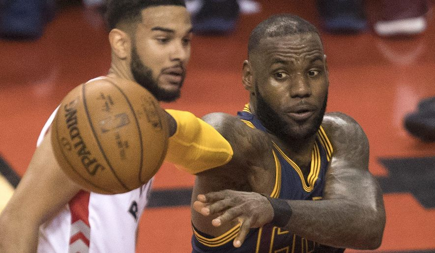 Cleveland Cavaliers' LeBron James, right, passes off the ball under the basket as Toronto Raptors guard Cory Joseph (6) looks on during the first half of Game 3 of an NBA basketball second-round playoff series in Toronto on Friday, May 5, 2017. (Fred Thornhill/The Canadian Press via AP)