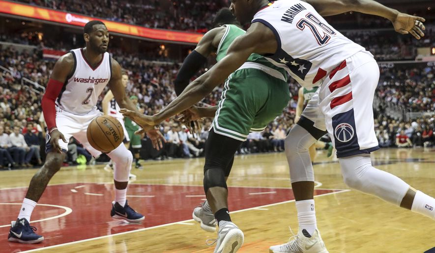 Washington Wizards center Ian Mahinmi (28), right, steals a ball from Boston Celtics forward Jaylen Brown (7) during the second half in Game 3 of a second-round NBA playoff series basketball game, Thursday, May 4, 2017, in Washington. Also pictured is Washington Wizards guard John Wall (2). (AP Photo/Andrew Harnik)