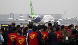 Attendees gather as a Chinese C919 passenger jet sits on the tarmac before its scheduled first flight at Pudong International Airport in Shanghai, Friday, May 5, 2017. China is touting the C919 as a rival to single-aisle jets the Airbus A320 and Boeing 737. The plane was originally due to fly in 2014 before being delivered to buyers in 2016, but has been beset by delays blamed on manufacturing problems. (AP Photo/Andy Wong, Pool)