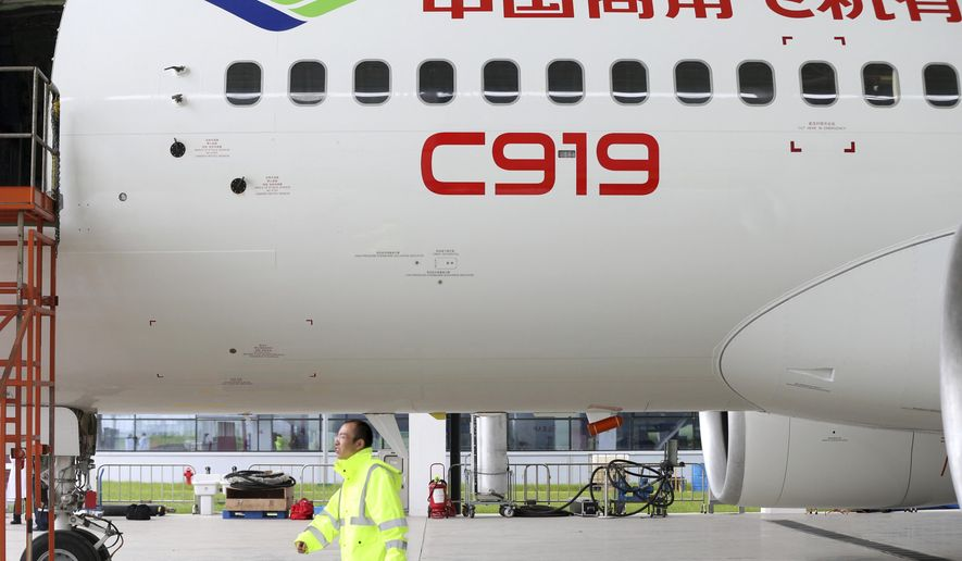 In this Thursday, May 4, 2017 photo, a worker walks past a COMAC C919 aircraft in an airplane hangar in Shanghai. China's first large homemade passenger jetliner is due to make its maiden flight from Shanghai later Friday. (Chinatopix via AP)