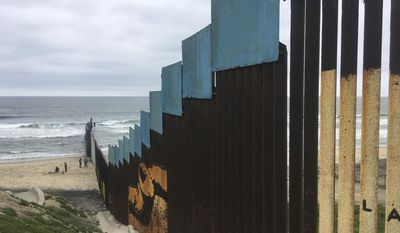 People stand on the Mexican side the U.S. border as a group of athletes from six countries swim across the border to Playas de Tijuana, Mexico, beach, on Friday, May 5, 2017. The swimmers from the United States, Mexico, Israel, New Zealand and South Africa were escorted by a Mexican Navy ship as they reached a beach in Tijuana, a short distance from a border fence that juts into the Pacific Ocean. (AP Photo/Elliot Spagat)