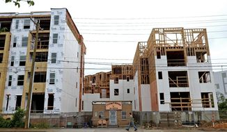 """The Thirsty Beaver at 1225 Central Avenue in Charlotte, NC has hung on through a disruptive construction project of new apartments that has literally turned it into Plaza Midwood's version of the house from the movie """"Up."""" The business is owned by brothers Mark and Brian Wilson. (Jeff Siner/The Charlotte Observer via AP)"""