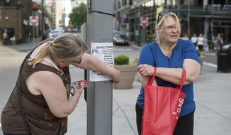 In this Sunday, April 30, 2017 photo, Jeanna Fisher, right, of Whitehall, and her longtime friend Jan Brophy, of Baldwin, post flyers asking for information on Fisher's daughter's last days in downtown Pittsburgh. Fisher is organizing volunteers to help her cover the downtown area in flyers asking for more information on her daughter Marley's last days before she died of a suspected heroin overdose in a Point State Park bathroom on April 9. (Stephanie Strasburg/Pittsburgh Post-Gazette via AP)