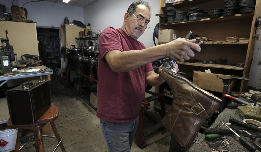 ADVANCE FOR MONDAY MAY 8, 2017- This photo taken April 7, 2017, shows modern day cobbler Javier Rodriguez repairing a pair of boots for a client out of Memphis at his east El Paso shoe repair shop. Rodriguez's family has a long history of shoe repair in the El Paso area. (Mark Lambie/The El Paso Times via AP)