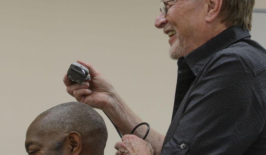 In this April 17, 2017, photo Stuart Stone gives Leanthony Edwards a hair cut at the Weigland Center in Salt Lake City. Stone as been volunteering his services giving haircuts to homeless individuals for some 20 years. (Steve Griffin/The Salt Lake Tribune via AP)
