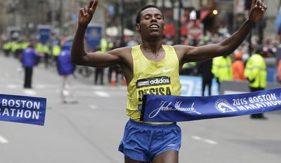 FILE - In this Monday, April 20, 2015 file photo, Lelisa Desisa, of Ethiopia, crosses the finish line to win the men's division of the Boston Marathon. On the 63rd anniversary of Roger Bannister breaking the four-minute mile, three elite athletes will attempt to do something arguably more extraordinary, run the first sub-two-hour marathon. Olympic marathon champion Eliud Kipchoge leads the attempt on Saturday, May 6, 2017 at Monza's Formula One racecourse, along with two-time Boston Marathon winner Lelisa Desisa, from Ethiopia, and Eritrean half-marathon world-record holder Zersenay Tadese. (AP Photo/Elise Amendola, File)