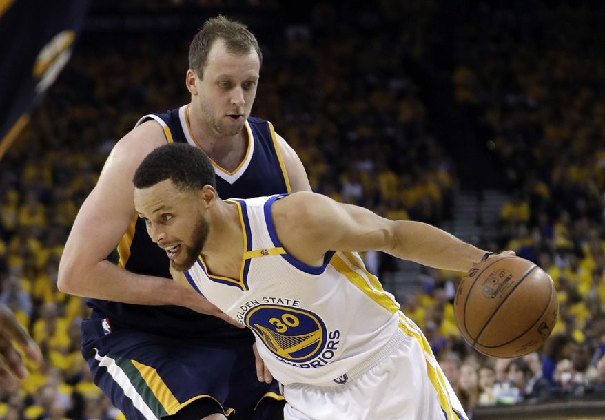 Golden State Warriors' Stephen Curry, bottom, dribbles past Utah Jazz's Joe Ingles during the first half in Game 2 of an NBA basketball second-round playoff series, Thursday, May 4, 2017, in Oakland, Calif. (AP Photo/Marcio Jose Sanchez)