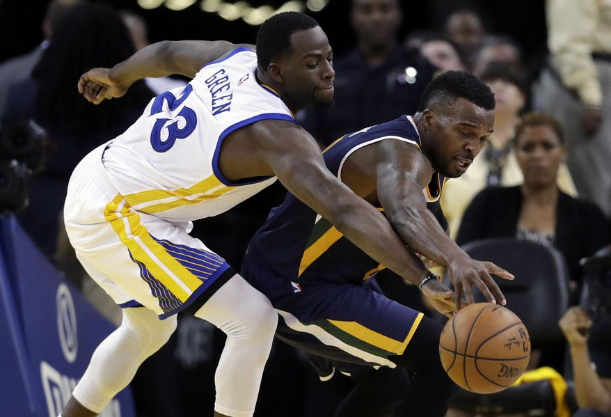 Golden State Warriors' Draymond Green, left, defends on Utah Jazz's Shelvin Mack during the first half in Game 2 of an NBA basketball second-round playoff series, Thursday, May 4, 2017, in Oakland, Calif. (AP Photo/Marcio Jose Sanchez)