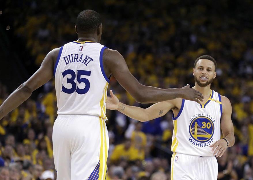Golden State Warriors' Stephen Curry, right, shakes hands with teammate Kevin Durant (35) during the first half in Game 2 of an NBA basketball second-round playoff series against the Utah Jazz, Thursday, May 4, 2017, in Oakland, Calif. (AP Photo/Marcio Jose Sanchez)