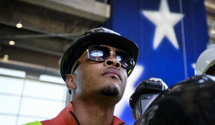 In this Tuesday, April 25, 2017, photo, rapper T.I. tours the Mercedes Benz Stadium, the new stadium for the Atlanta Falcons NFL football team under construction in Atlanta. In a recent interview, The Associated Press spoke with T.I. about his social justice efforts and upcoming music. (AP Photo/David Goldman)