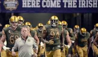 FILE - In this Nov. 12, 2016, file photo, Notre Dame coach Brian Kelly, left, runs onto the field with his players before an NCAA college football game against Army in San Antonio. This is a first for Notre Dame coach Brian Kelly. He has been a college head football coach for the last 27 years and until now he had never reached this fork in his career path: Get better or get fired. (AP Photo/Darren Abate, File)
