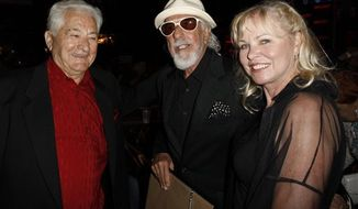 FILE - In this June 26, 2008 file photo Lou Adler, center, is joined by Mario Maglieri, left, and Michelle Phillips, pose for photos at a Sunset Strip Music Festival tribute event in Los Angeles. Maglieri, the Hollywood entrepreneur who doubled as a godfather figure to generations of rock stars from the Doors' Jim Morrison to Guns 'N Roses' Axl Rose, has died at age 93. For decades Maglieri, ran two of Hollywood's most popular Sunset Strip nightclubs the Whiskey A Go Go and Rainbow Bar & Grill. (AP Photo/Matt Sayles, File)