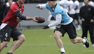 Carolina Panthers' Christian McCaffrey, right, takes a handoff from Garrett Gilbert, left, during the NFL football team's rookie camp in Charlotte, N.C., Friday, May 5, 2017. The Panthers hope that McCaffrey's being raise in an NFL family, his father was a three-time Super Bowl champion, will help make the transition from college that much easier. (AP Photo/Chuck Burton)