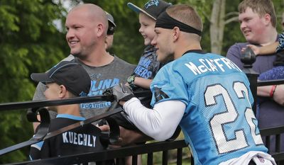 Carolina Panthers' Christian McCaffrey (22) poses for a photo with fans before practice at the NFL football team's rookie camp in Charlotte, N.C., Friday, May 5, 2017. The Panthers hope that McCaffrey's being raise in an NFL family, his father was a three-time Super Bowl champion, will help make the transition from college that much easier. (AP Photo/Chuck Burton)