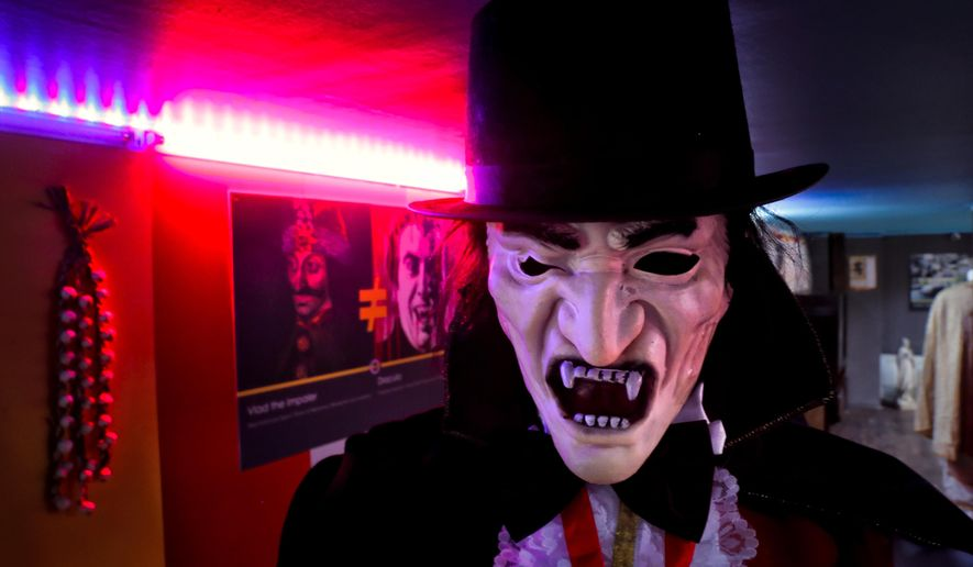 In this Thursday, May 4, 2017, photo mannequin depicting Dracula is backdropped by a poster attempting to differentiate Bram Stoker's character from Romanian medieval ruler Vlad the Impaler, seen at left, at the newly opened Bucharest Kitsch Museum, in Bucharest, Romania. The Kitsch Museum opens for visitors on Friday, May 5, 2017. (AP Photo/Vadim Ghirda)