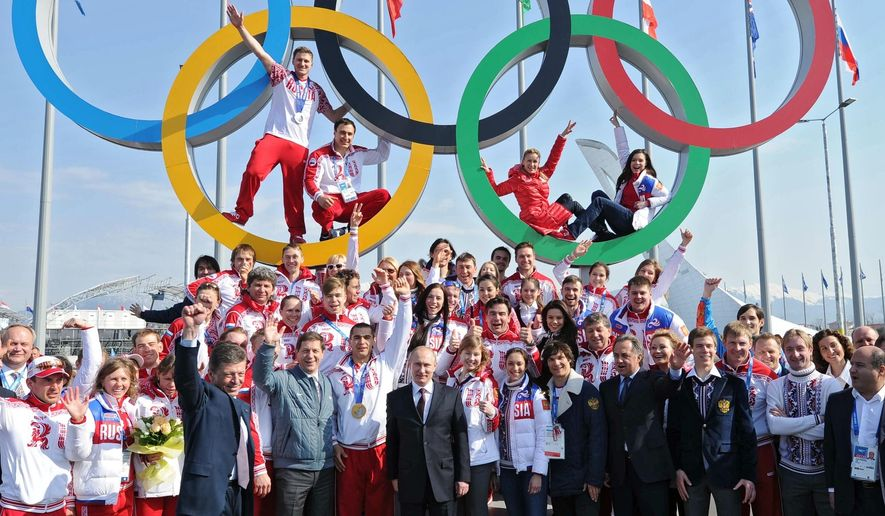 FILE - A Monday, Feb. 24, 2014, file photo showing Russian President Vladimir Putin, center, posing with Russian Olympic medal winners after Sochi 2014 Winter Olympics in Sochi, Russia. The Russian president told Olympic historian David Miller in an exclusive interview made available on Friday May 5, 2017, that his country has plenty of candidates capable of hosting the Summer Games, not just Moscow. (Mikhail Klimentyev/Pool Photo via AP)