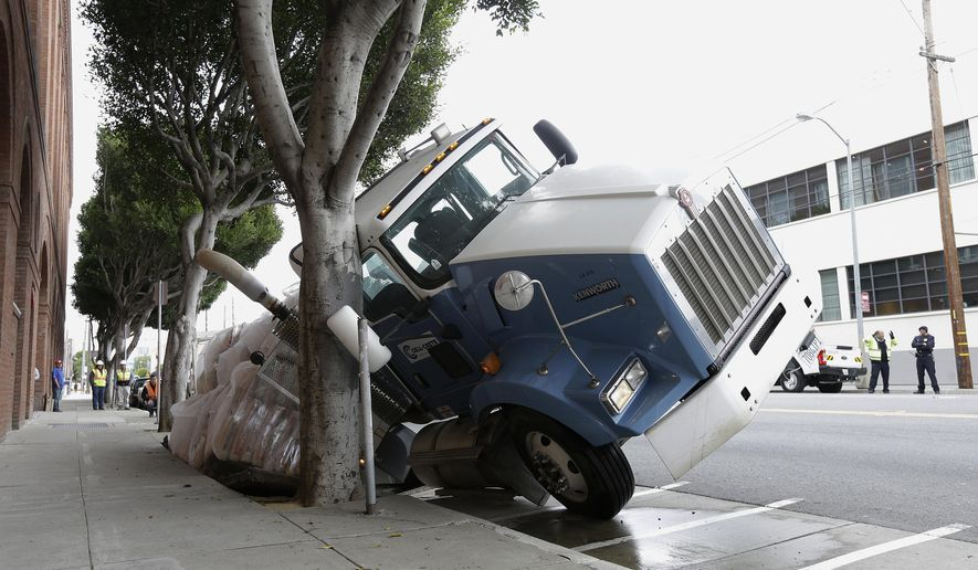 A big rig truck is stuck in a sinkhole in San Francisco, Friday, May 5, 2017. A truck driver escaped unharmed early Friday after a massive sinkhole started swallowing his big rig on a San Francisco street. (AP Photo/Jeff Chiu)