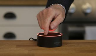In this March 2, 2016, file photo, David Limp, Amazon Senior Vice President of Devices, pushes down on an Echo Dot in San Francisco. (AP Photo/Jeff Chiu, File)