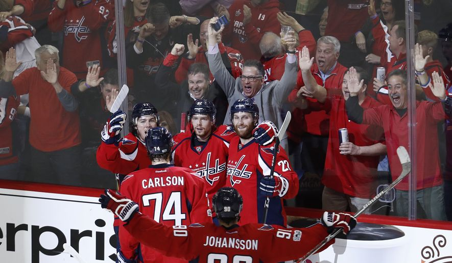 Washington Capitals center Evgeny Kuznetsov (92), from Russia, celebrates scoring the game winning goal against the Pittsburgh Penguins with teammates, T.J. Oshie (77), John Carlson (74), Marcus Johansson (90), from Sweden, and Karl Alzner (27) during the third period of Game 5 in the second-round of the NHL hockey Stanley Cup playoffs, Saturday, May 6, 2017, in Washington. The Capitols won 4-2. (AP Photo/Carolyn Kaster)