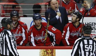 Washington Capitals head coach Barry Trotz calls to linesman Steve Barton (59) as linesman Jonny Murray (95) stands left, during the third period of Game 5 in the second-round of the NHL hockey Stanley Cup playoffs, Saturday, May 6, 2017, in Washington. The Capitals won 4-2. On the bench form left, Washington Capitals left wing Alex Ovechkin (8), from Russia, left wing Andre Burakovsky (65), from Austria, and defenseman Kevin Shattenkirk (22). (AP Photo/Carolyn Kaster)