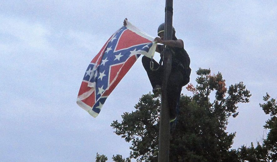 FILE - In this June, 27, 2015 file photo, Bree Newsome, of Charlotte, N.C., removes the Confederate flag from a Confederate monument at the Statehouse in Columbia, S.C. Newsome was taken into custody when she came down. A new generation of black women is moving to take and keep a place at the forefront of the fight against racial bias. Black women have not been strangers to past protests. But historians say they have often been overshadowed, first by white women during the suffragette movement and then by the black men who were lionized during the civil rights movement. (AP Photo/Bruce Smith, File)