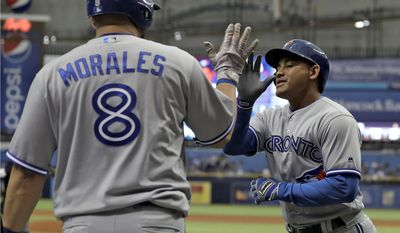 Toronto Blue Jays' Ezequiel Carrera, right, high fives Kendrys Morales after Carrera hit a home run off Tampa Bay Rays starting pitcher Jake Odorizzi during the first inning of a baseball game, Saturday, May 6, 2017, in St. Petersburg, Fla. (AP Photo/Chris O'Meara)