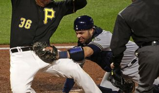 Pittsburgh Pirates' Jose Osuna (36) is tagged out by Milwaukee Brewers catcher Manny Pina with umpire Jim Reynolds, right, making the call in the fourth inning of a baseball game in Pittsburgh, Friday, May 5, 2017. Osuna was out attempting to score on a single by Pirates' Wade LeBlanc. (AP Photo/Gene J. Puskar)