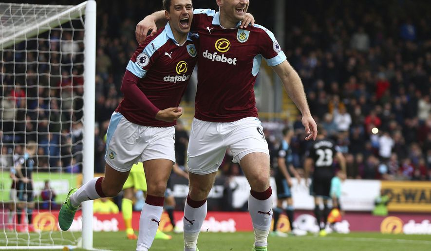 Burnley's Sam Vokes celebrates scoring with team mate Matt Lowton during the Premier League soccer match between Burnley and West Bromwich Albion at Turf Moor, Burnley, England. Saturday May 6, 2017. (Barrington Coombs/PA via AP)