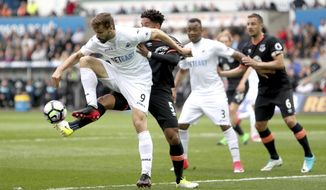 Swansea City's Fernando Llorente, left, and Everton's Ashley Williams compete for the ball during the English Premier League soccer match, Swansea City against Everton at the Liberty Stadium, Swansea, Wales,  Saturday May 6, 2017. (David Davies/PA via AP)
