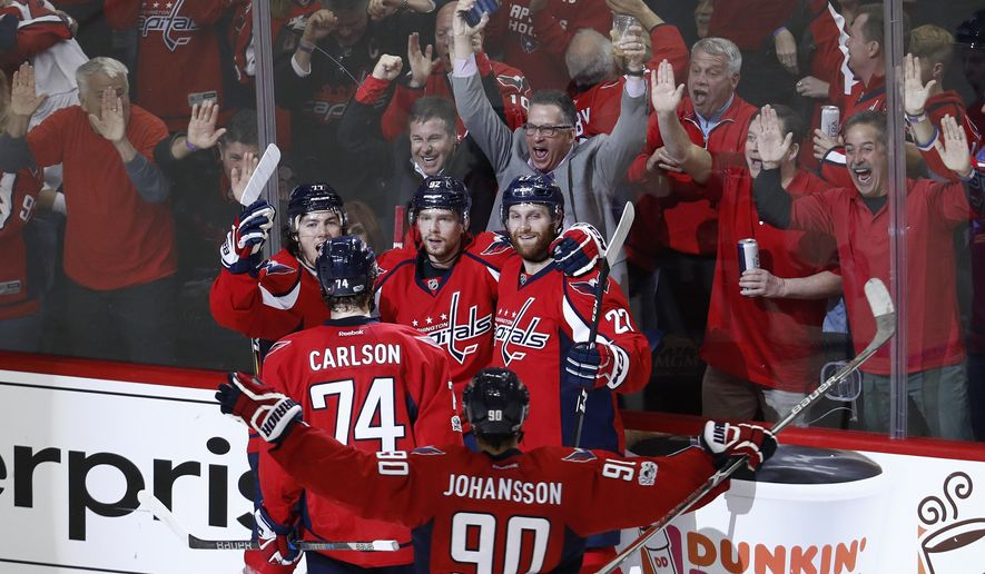 Washington Capitals center Evgeny Kuznetsov (92), from Russia, celebrates scoring the game winning goal against the Pittsburgh Penguins with teammates, T.J. Oshie (77), John Carlson (74), Marcus Johansson (90), from Sweden, and Karl Alzner (27) during the third period of Game 5 in the second-round of the NHL hockey Stanley Cup playoffs, Saturday, May 6, 2017, in Washington. The Capitals won 4-2. (AP Photo/Carolyn Kaster) ** FILE **