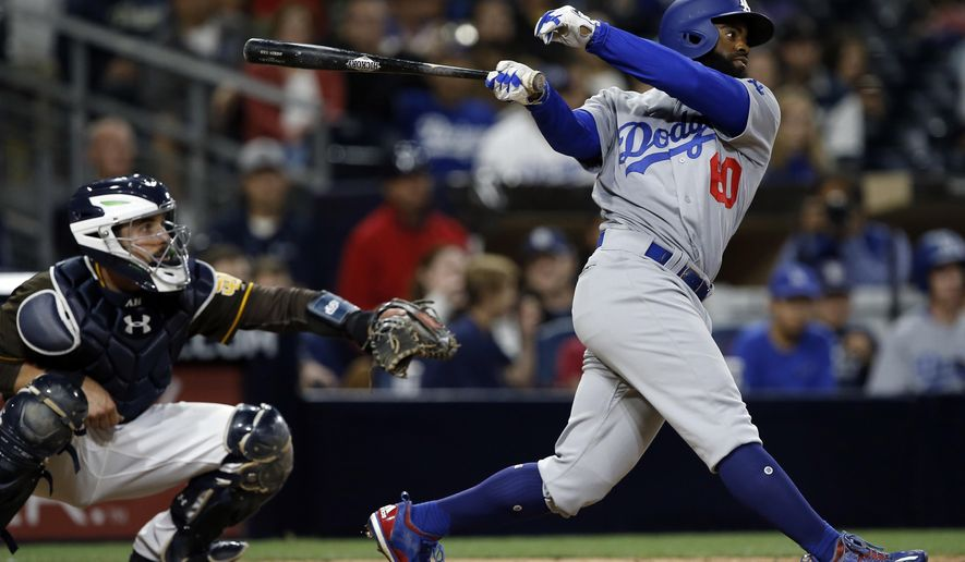 Los Angeles Dodgers' Andrew Toles, right, hits a two-run double with San Diego Padres catcher Austin Hedges watching during the seventh inning of a baseball game in San Diego, Friday, May 5, 2017. (AP Photo/Alex Gallardo)