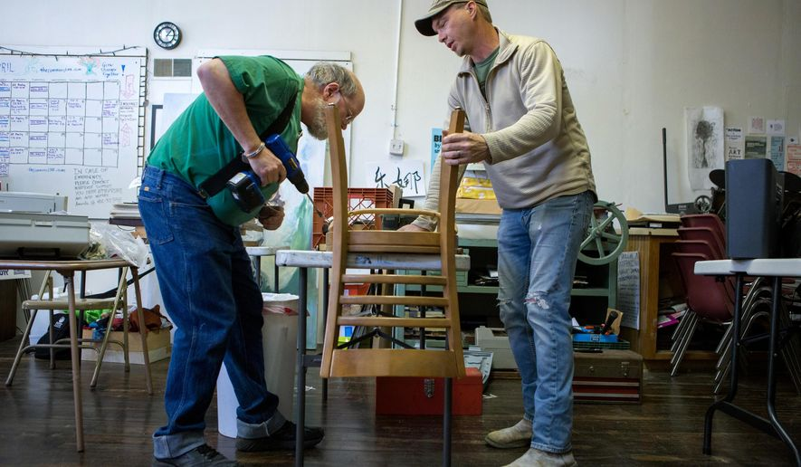 In this Sunday, April 23, 2017 photo, volunteer repairmen Larry James, left, and Justin Orem work on a chair at the Lincoln Repair Cafe, in Lincoln, Neb. (Calla Kessler/Omaha World-Herald via AP)