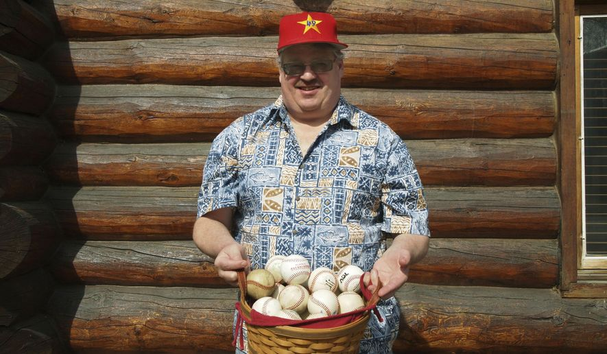 ADVANCE FOR WEEKEND EDITIONS - In this Sunday, April 30, 2017, photo, Jim Dixon poses with his baseball collection in front of his home in Fairbanks, Alaska. An avid baseball fan, Dixon not only runs the website D3baseball.com, he sits on the Alaska Goldpanners board of directors. (Kevin Baird/Fairbanks Daily News-Miner via AP)