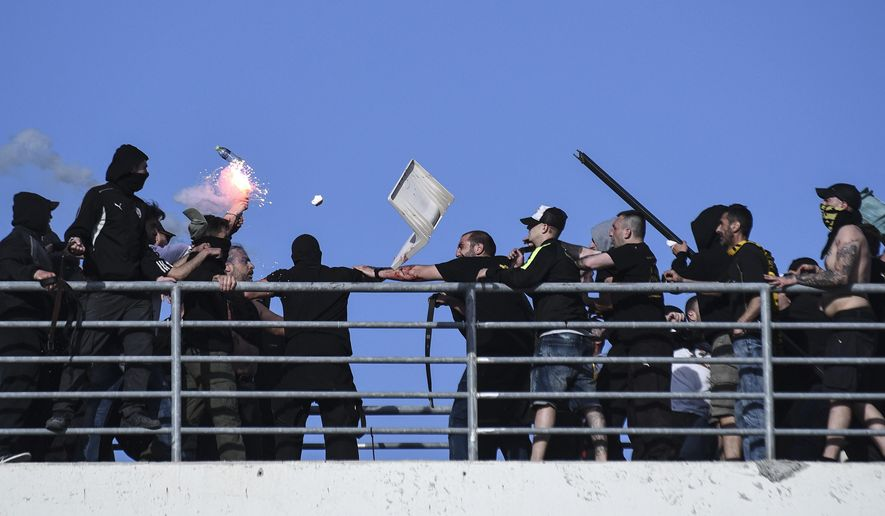 Soccer fans clash at a tribune of Panthessaliko stadium, ahead of the Greek Cup soccer final between AEK Athens' and PAOK in Volos, central Greece, on Saturday, May 6, 2017. (AP Photo/Giannis Papanikos)
