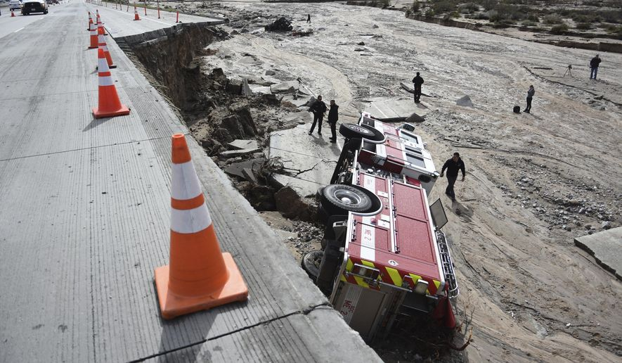 FILE - In this Feb. 18, 2017 file photo, officials look over the scene at Interstate 15 in the Cajon Pass, Calif., where part of the freeway collapsed due to heavy rain. A state $5 billion annual plan raises fuel taxes and vehicle fees to pay for repairs to state and local roads, while also providing money for public transit and biking and walking trails. (David Pardo/The Daily Press via AP, file)