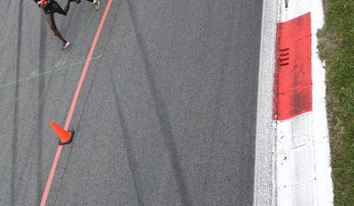 Athletes compete in the marathon at the Monza Formula One racetrack, Italy, Saturday, May 6, 2017. Olympic marathon champion Eliud Kipchoge won the race and was 26 seconds from making history on Saturday but in the end the Olympic champion was just short of becoming the first person to run a marathon in less than two hours. Kipchoge ran the 26.2 miles (42.2 kilometers) in 2 hours and 25 seconds, beating Dennis Kimetto's world record of 2:02:57, but the Kenyan failed to run the first sub-two hour marathon. The attempt at Monza's Formula One racecourse did not go down as an official world record, sanctioned by the IAAF, due to variables like pacers entering mid-race and drinks being given to runners via mopeds. (AP Photo/Luca Bruno)