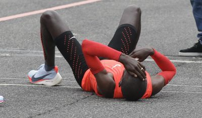 Olympic marathon champion Eliud Kipchoge lies down after crossing the finish line of a marathon at the Monza Formula One racetrack, Italy, Saturday, May 6, 2017. Kipchoge was 26 seconds from making history on Saturday but in the end the Olympic champion was just short of becoming the first person to run a marathon in less than two hours. Kipchoge ran the 26.2 miles (42.2 kilometers) in 2 hours and 24 seconds, beating Dennis Kimetto's world record of 2:02:57, but the Kenyan failed to run the first sub-two hour marathon. (AP Photo/Luca Bruno)
