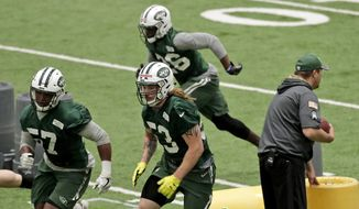 New York Jets' Dylan Donahue, center, runs a drill during NFL football football rookie minicamp, Friday, May 5, 2017, in Florham Park, N.J. (AP Photo/Julio Cortez) **File**