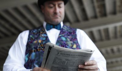A fan looks over a program before the 143rd running of the Kentucky Derby horse race at Churchill Downs Saturday, May 6, 2017, in Louisville, Ky. (AP Photo/John Minchillo)