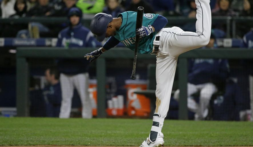 Seattle Mariners' Jarrod Dyson leaps to avoid a wild pitch from Texas Rangers starting pitcher Yu Darvish in the seventh inning of a baseball game, Friday, May 5, 2017, in Seattle. (AP Photo/Ted S. Warren)